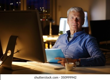 Portrait of senior financial advisor sitting at office and working late. Busy businessman holding in hand documents while analyzing data on computer.