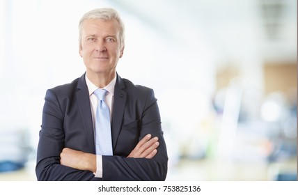 Portrait of a senior financial advisor standing with arms crossed at the office.
