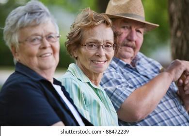 Portrait of senior friends sitting together in park
