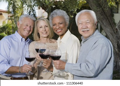 Portrait of senior friends toasting glass of red wine