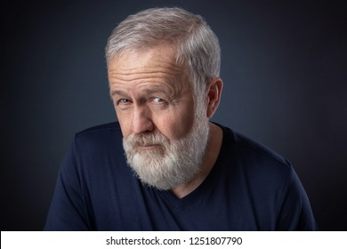 Portrait of senior with gray beard and a deep look