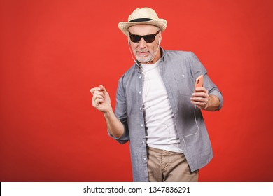 Portrait of senior happy cheerful elderly man dancing and listening music witn phone and headphones  isolated against red background.