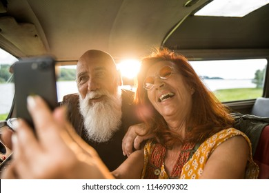 Portrait of an senior hipster couple doing a selfie with a phone inside their vintage van parked near a lake. He's tattooed with a white beard, she's red hair.
