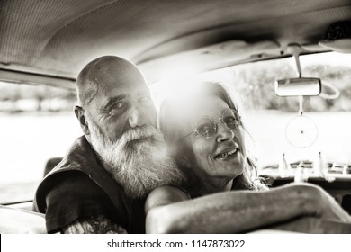 Portrait of an senior hipster couple inside their vintage van parked near a lake. He's tattooed with a white beard. black and white