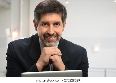 Portrait of senior Hispanic businessman using laptop inside office building