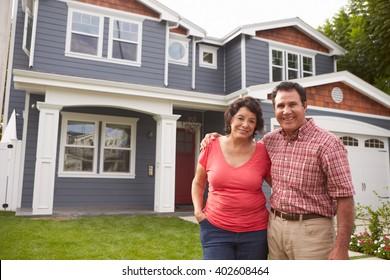Portrait Of Senior Hispanic Couple Standing Outside House