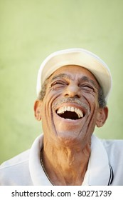 portrait of senior hispanic man with white hat looking up against green wall and smiling. Vertical shape, copy space