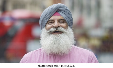 Portrait of senior Indian man in a turban smiling to camera on the street