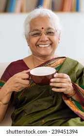 Portrait of senior Indian woman in sari drinking tea