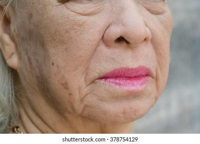Portrait of senior lady applying red lipstick
