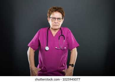 Portrait of senior lady doctor angry with hands in pockets  on black background with copyspace advertising area