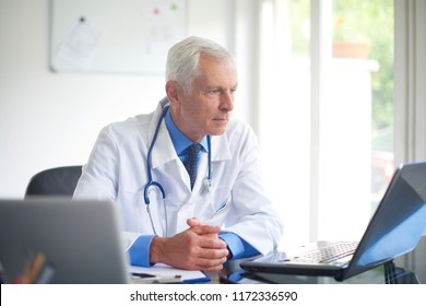 Portrait of senior male doctor working on laptop while sitting in consulting room.