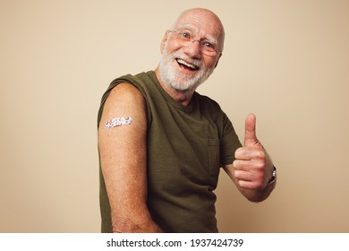 Portrait of a senior male smiling and showing thumbs up after getting a vaccine. Mature man with white beard sitting against brown background feeling positive after receiving immunity vaccination.