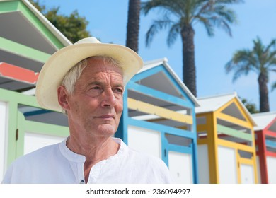 Portrait senior man at beach with colorful wooden huts