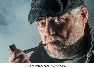 Portrait of a senior man with beard, flat cap, tobacco pipe and leather jacket. Concept: portrait with eye contact