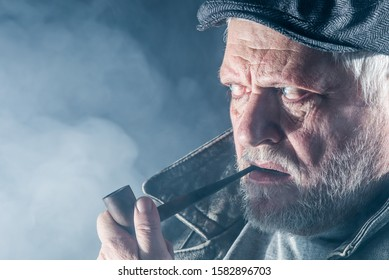 Portrait of a senior man with beard, flat cap, tobacco pipe and leather jacket.