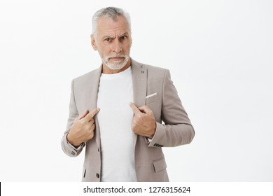 Portrait of senior man being accused in commiting crime standing insulted and intense pointing at himself with serious displeased and offended expression asking question at camera over gray wall