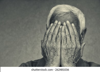 portrait of senior man covering the face with his hands. black and white image