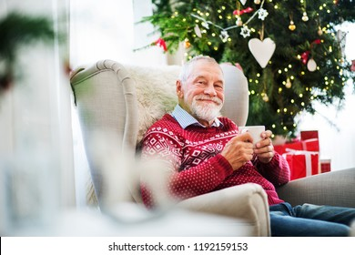 A portrait of senior man with a cup sitting on armchair at home at Christmas time.
