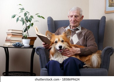 portrait of  senior man with dog corgi sitting in an armchair and reading books. leisure old man