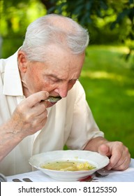 Portrait of a senior man eating a soup outdoor