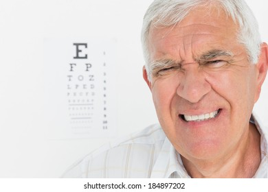 Portrait of a senior man with eye chart in the background at medical office