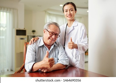 Portrait of senior man in eyeglasses sitting at the table and showing thumbs up together with his Asian female doctor standing near by him at hospital