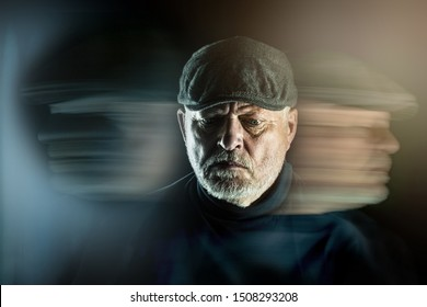 Portrait of a senior man with flat cap in front of black background. Ghostly faces surround him. Concept: surreal portraits