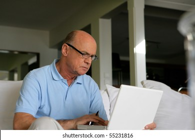 Portrait of a senior man in front of a laptop computer