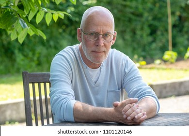a portrait of senior man with glasses, outdoors