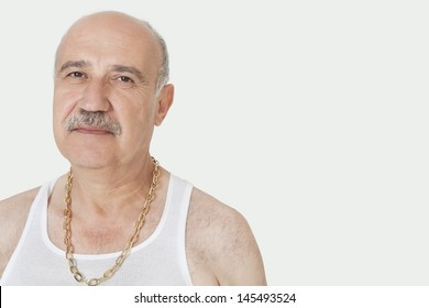 Portrait of senior man with gold chain over gray background