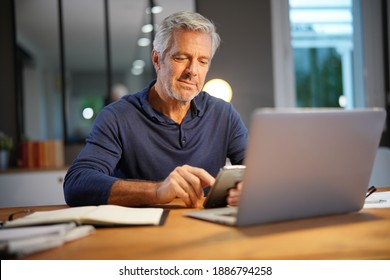 Portrait of senior man with grey hair connected with laptop