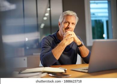 Portrait d'homme âgé avec cheveux gris relié à un ordinateur portable