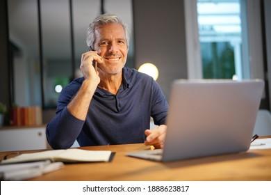 Retrato de anciano con pelo gris conectado con laptop