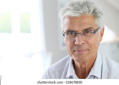 Portrait of senior man with grey hair wearing eyeglasses