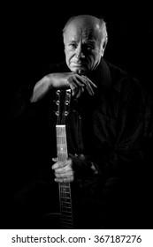 Portrait of senior man with guitar at black background