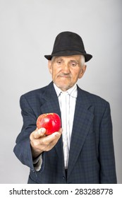 Portrait of a senior man with hat offering a red apple over grey background