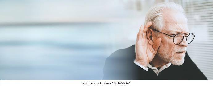 Portrait of senior man having hearing problems; panoramic banner
