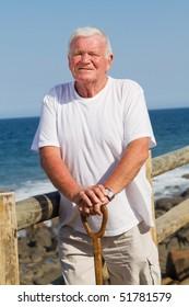 portrait of a senior man holding cane on beach