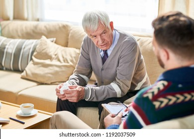 Portrait of senior man holding tissues  sharing mental problems with psychologist during therapy session, copy space