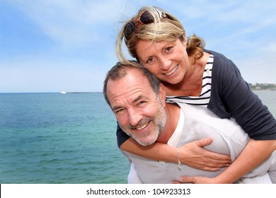 Portrait of senior man holding woman on his back