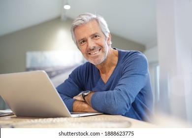 Portrait d'homme âgé à la maison travaillant sur un ordinateur portable