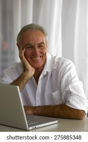 Portrait of senior man leaning on a table in front of a laptop with hand on his cheek.