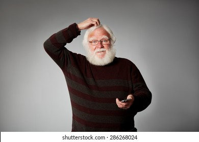 Portrait of senior man with a mobile phone looking confused over grey background