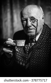Portrait of Senior Man with monocle and a coffee cup