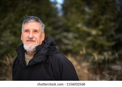 Portrait of a senior man, outdoor on a snowy forest path. Enjoying the crisp fresh air, watching the Sun go down.