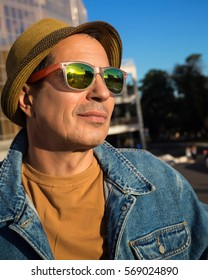 Portrait of a senior man outdoors on a summer day.handsome maturing man wearing hat,trendy jeans coat  and sunglasses.