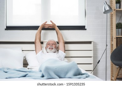 Portrait of a senior  man in pajamas waking up in bed and stretching his arms. Concept of energy from the early morning of a single retired man. Copy space image