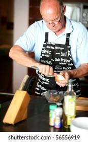 Portrait of a senior man peeling an onion