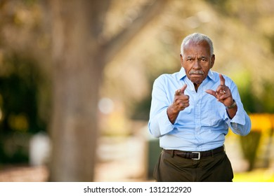 Portrait of senior man playfully pointing at the camera.